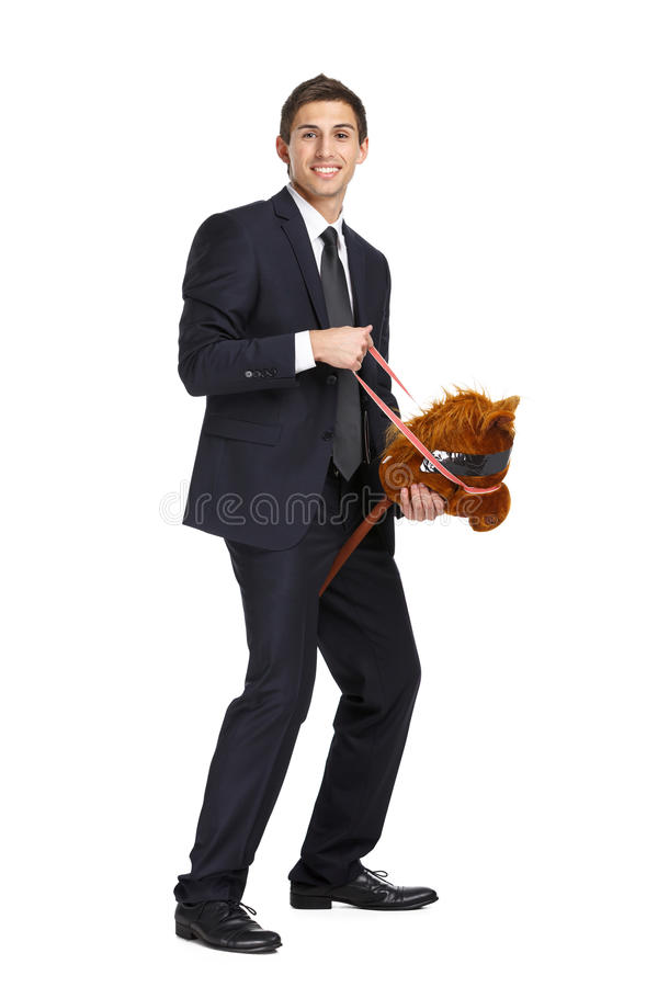 Businessman riding the toy horse. Full-length portrait of businessman riding the toy horse, isolated on white stock images
