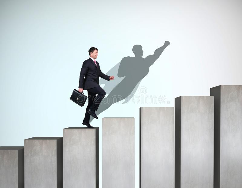 Businessman rise up on the career ladder with superhero shadow on the wall. stock photography