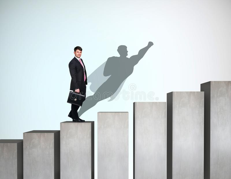 Businessman rise up on the career ladder with superhero shadow on the wall. royalty free stock photos