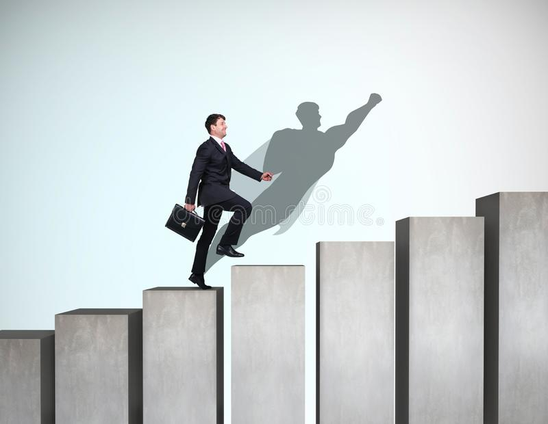 Businessman rise up on the career ladder with superhero shadow on the wall. stock photo
