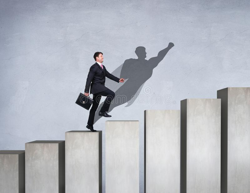 Businessman rise up on the career ladder with superhero shadow on the wall. royalty free stock image