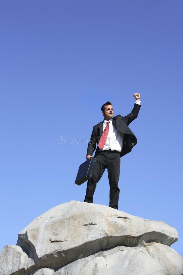 Businessman on rock stock photo