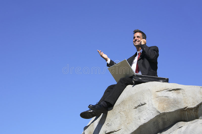Businessman on a rock stock photography