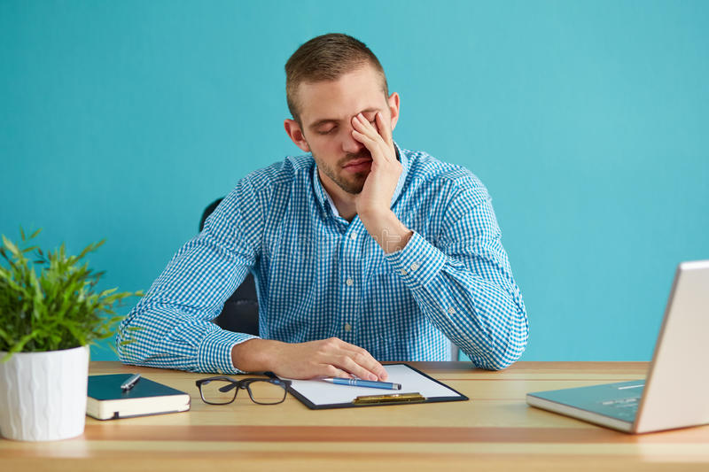 Businessman rubbing his eye. Young tired businessman rubbing his eye, in office stock photo