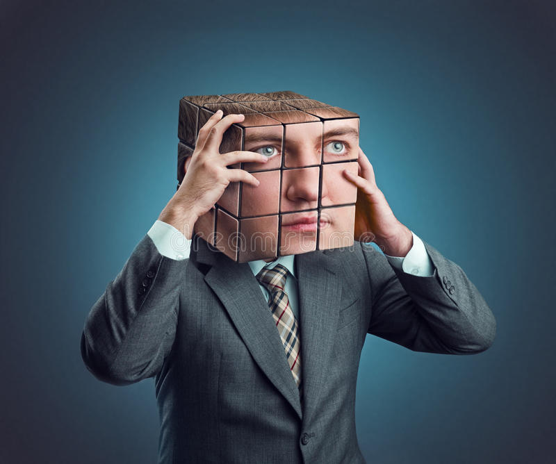 Businessman with rubik cube head. Businessman wearing in suit holding his rubik cube head royalty free stock photography