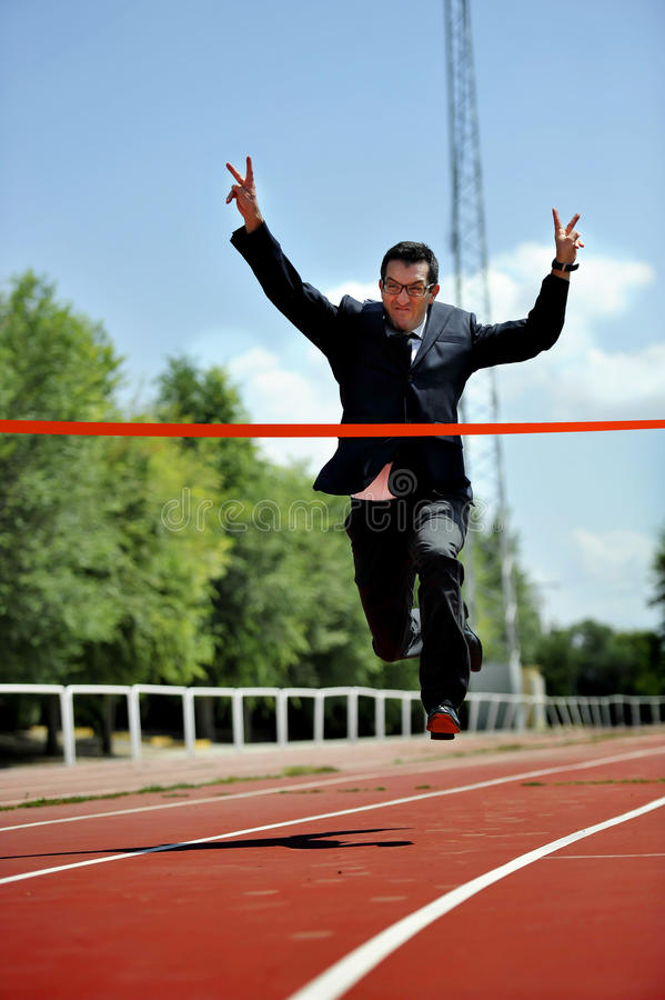 Businessman running on athletic track celebrating victory in work success concept stock images