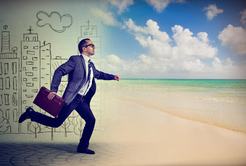Businessman running away from a life in a city to the sunny beach stock photos