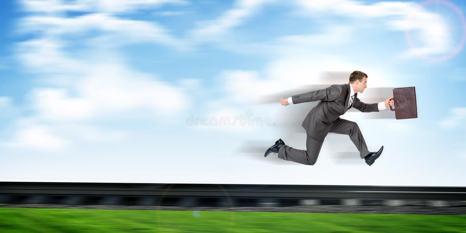 Businessman running away. Businessman with suitcase running away on rail-track stock photo