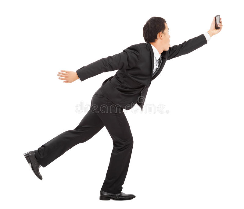 Businessman running busily and holding a smart phone stock photo