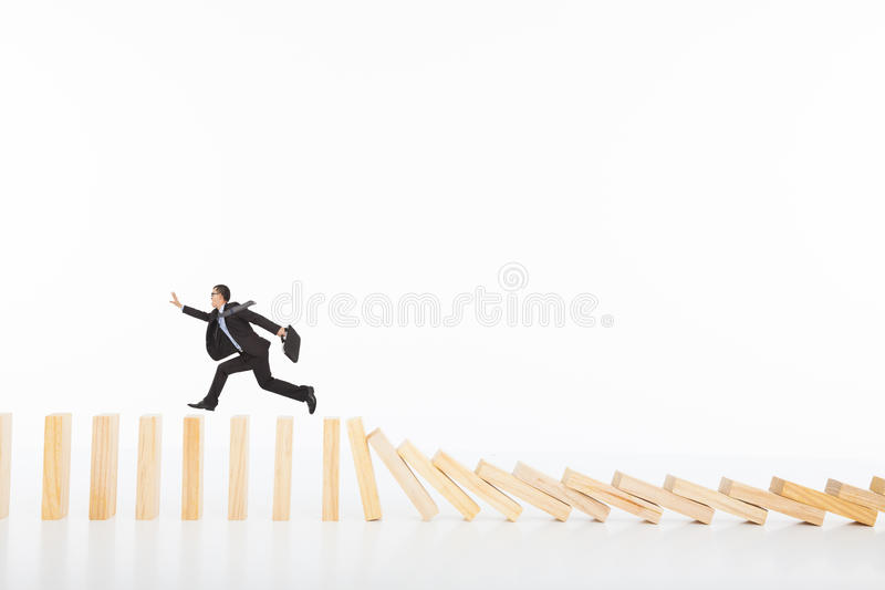 Businessman running and catching on toppling dominoes stock photography