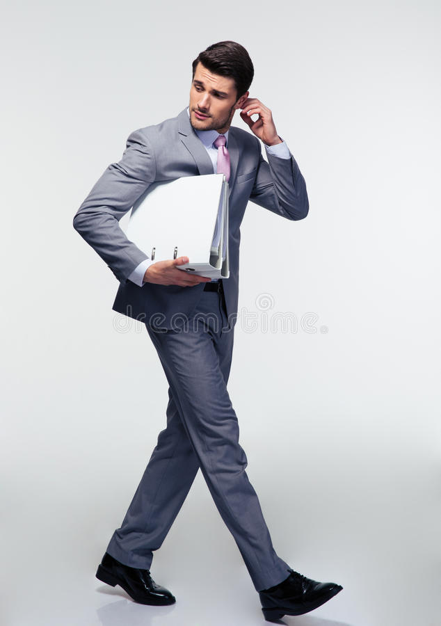 Businessman running with folders. Full length portrait of a businessman running with folders over gray background. Looking away stock photo