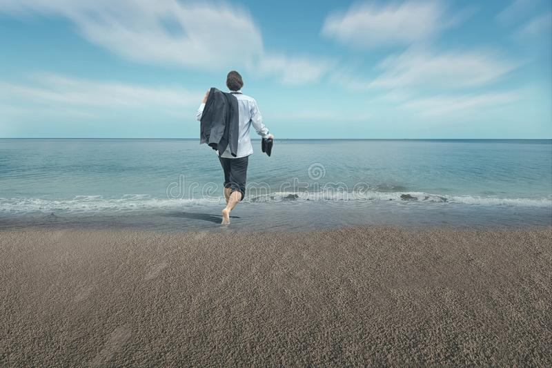 Businessman with feet in water. Businessman running happy to the sea . The concept of take a necessary break and enjoy it royalty free stock images