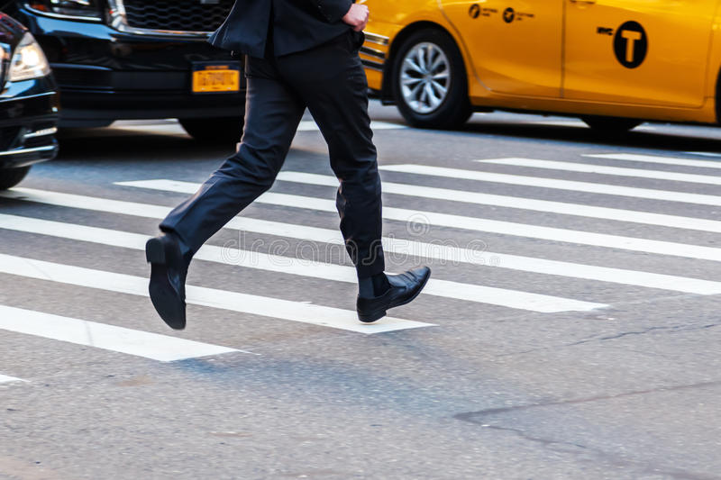 Businessman running over a street in Manhattan, NYC. Running businessman crossing a street in the city of Manhattan, NYC royalty free stock photo