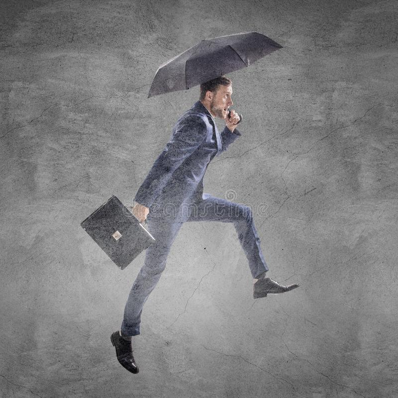 Businessman running with umbrella and briefcase. stock photo