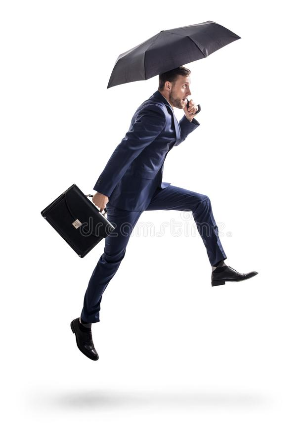 Businessman running with umbrella and briefcase. stock image
