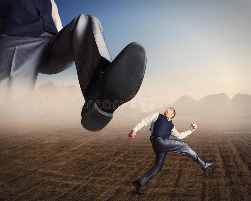 Businessman runs from a big foot. Businessman runs in a desert from a big foot royalty free stock images