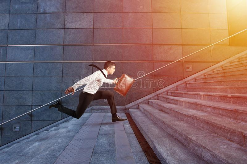 Businessman runs fast over a modern staircase. Businessman runs fast to office over a modern staircase stock image