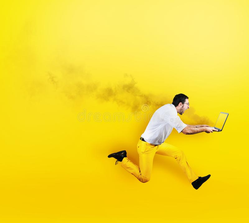 Businessman runs with laptop on fire in hand. Yellow style royalty free stock image