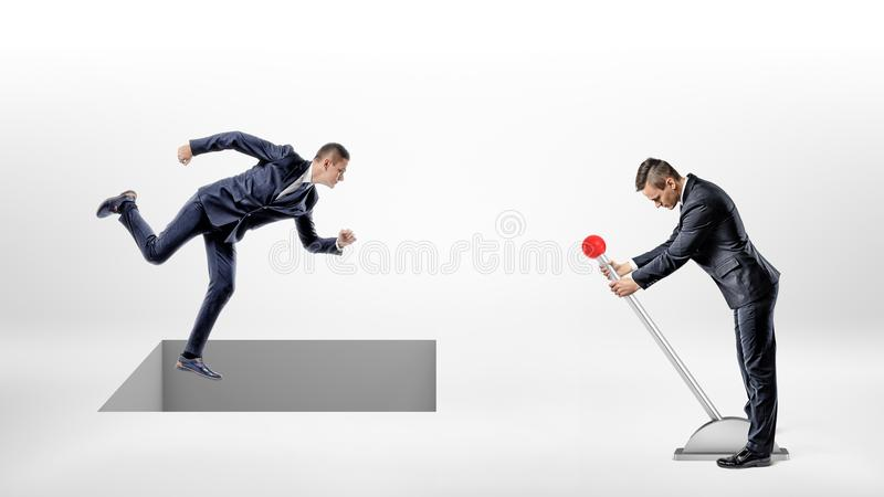 A businessman runs on white ground while a square hole controlled by a man on a lever opens right under his feet. Finance trap. Credit rate robbery. Corporate stock photography