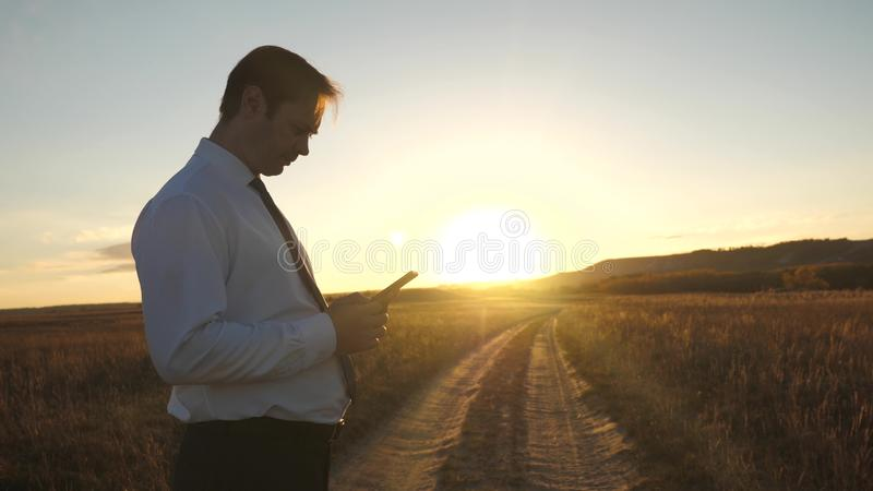 Businessman`s fingers touch screen of tablet, smartphone. male hands are holding a tablet and checking emails in park at. Businessman`s fingers touch screen of stock photography