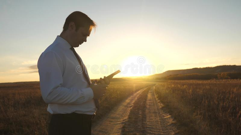 Businessman`s fingers touch screen of tablet, smartphone. male hands are holding a tablet and checking emails in park at. Businessman`s fingers touch screen of royalty free stock image