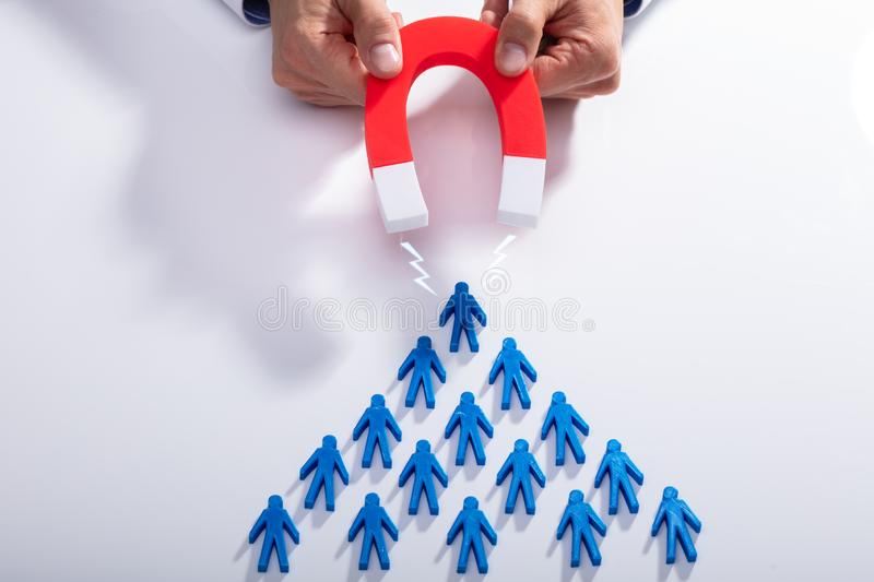 Businessman Attracting Blue Team With Horseshoe Magnet stock photo