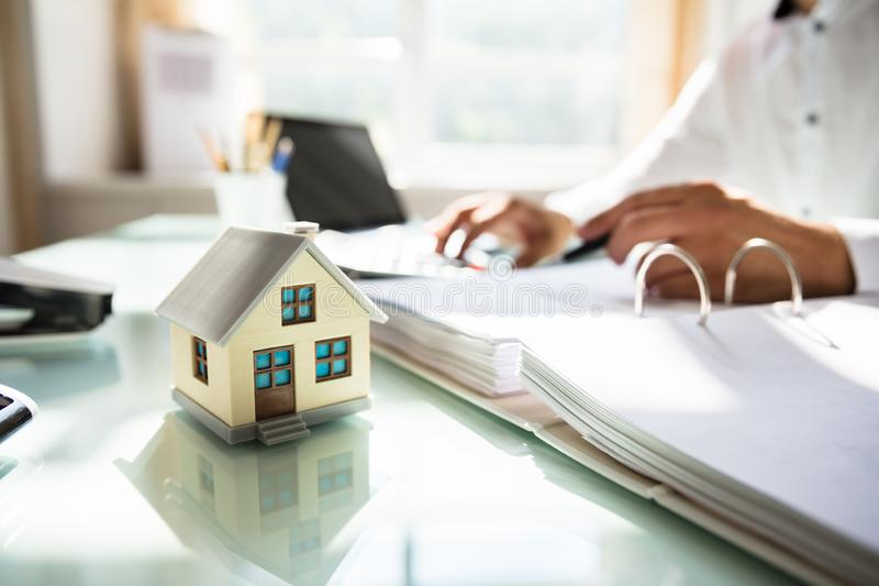Businessman`s hand calculating invoice. With house model in office royalty free stock images