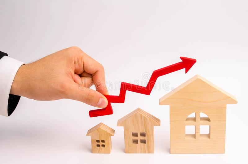 Businessman`s hand holds the red arrow up above the houses. The concept of growth in demand for real estate. Increase in the valu royalty free stock image