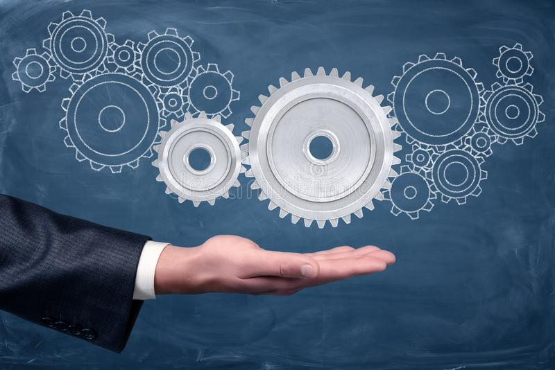 A businessman`s hand holds two connected gears on a blackboard background with many other gears drawn on it. royalty free stock photo