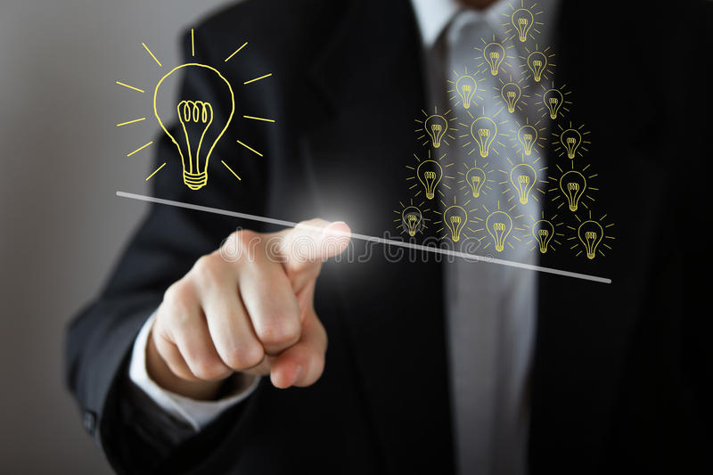 Businessman's hand pressing the icon on virtual screen drawing many small idea have more weight than one big idea stock photos