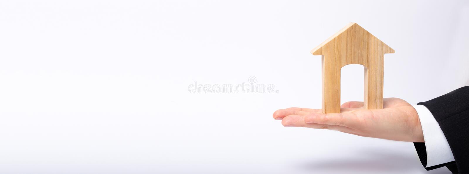 The businessman`s hand stretches a wooden house with a large doorway. The concept of commercial real estate. The purchase and sale of residential buildings stock photography