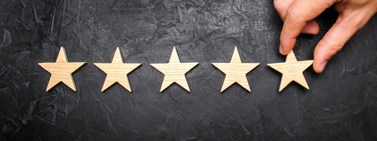 The businessman`s hand in the suit holds the fifth star. Get the fifth star. The concept of the rating of hotels and restaurants. The evaluation of critics and royalty free stock photo