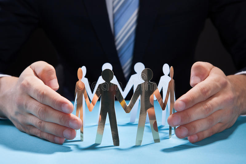 Businessman's hands protecting team of paper people on desk royalty free stock image