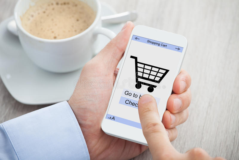 Businessman's hands shopping online through smartphone. Closeup of businessman's hands shopping online through smartphone at desk royalty free stock image