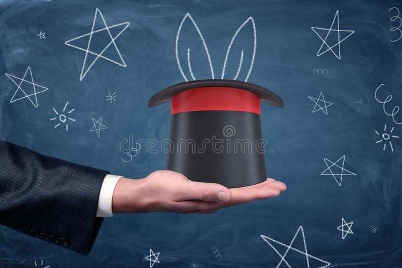 A businessman`s palm with a magician`s hat resting on it and drawings of stars and rabbit ears around. stock images
