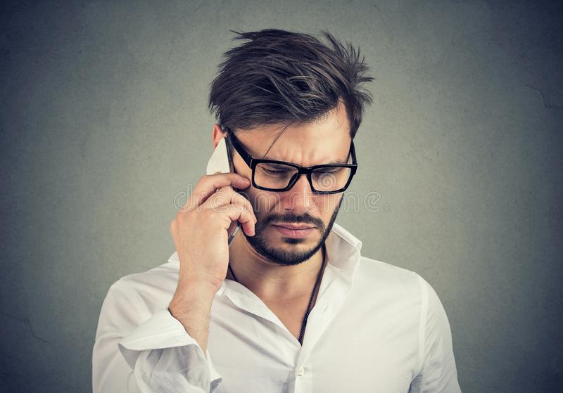 Businessman with sad expression talking on mobile phone looking down stock photos