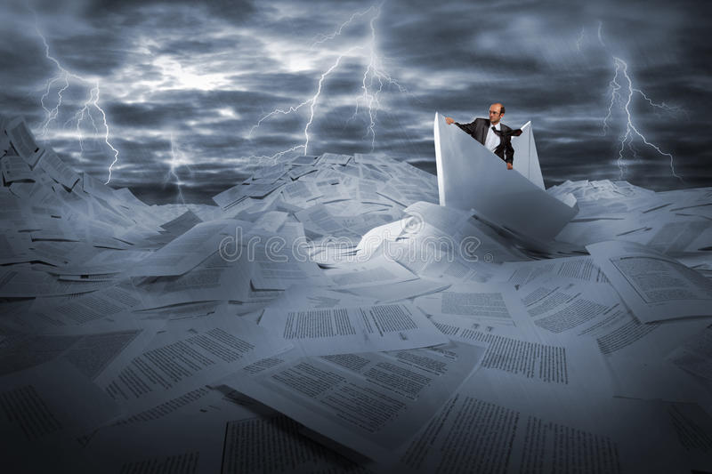 Businessman sailing in stormy papers sea royalty free stock photos