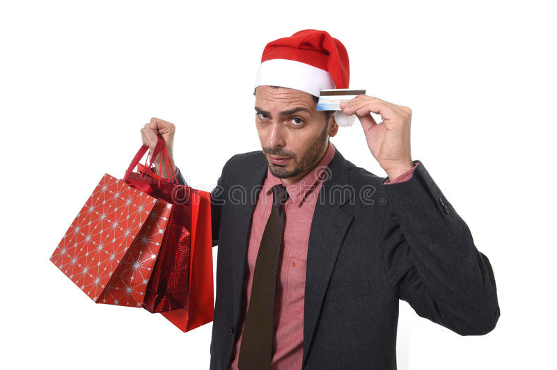 Businessman in Santa Claus Christmas hat holding sopping bags and credit card in worried and stress. Young attractive business man in Santa Claus hat holding royalty free stock image