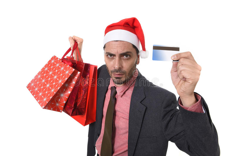Businessman in Santa Claus Christmas hat holding sopping bags and credit card in worried and stress. Young attractive business man in Santa Claus hat holding royalty free stock photography