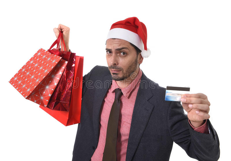 Businessman in Santa Claus Christmas hat holding sopping bags and credit card in worried and stress. Young attractive business man in Santa Claus hat holding stock image
