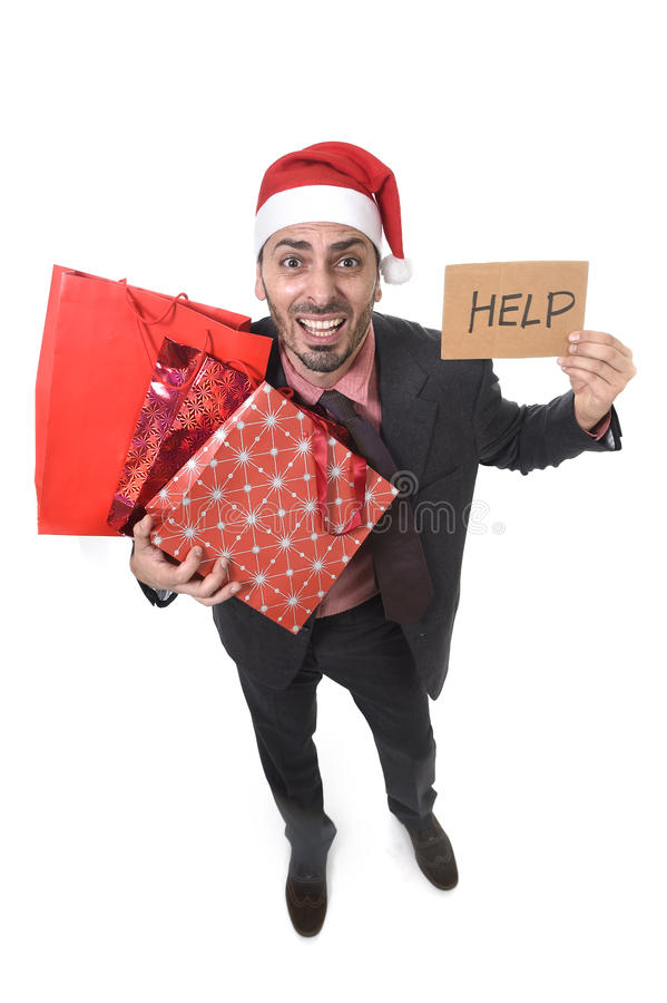 Businessman in Santa Claus hat holding shopping bags asking for help with cardboard sign worried. Young attractive business man in Santa Claus hat holding stock photos