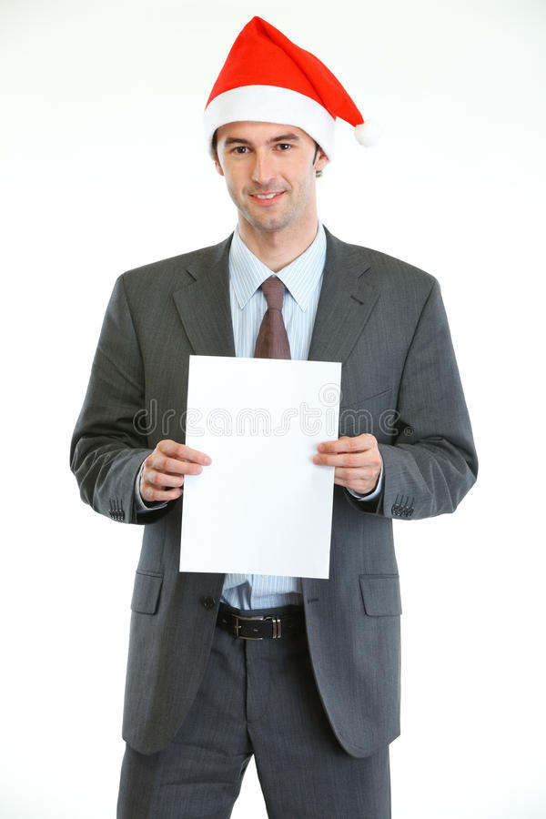 Businessman in Santas hat showing blank paper royalty free stock photo
