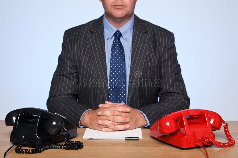 Businessman sat at desk with two telephones. stock image