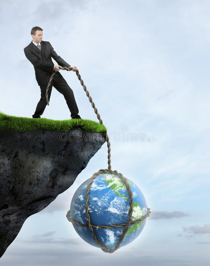 Businessman saving Earth from falling of the cliff stock photography