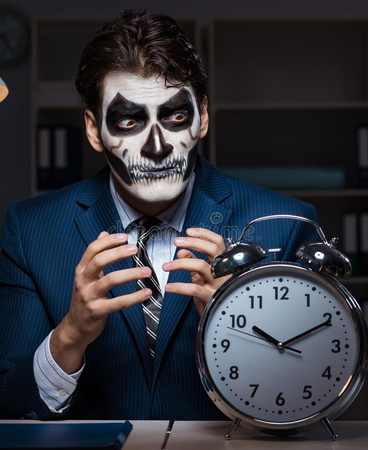 Businessman with scary face mask working late in office royalty free stock photography