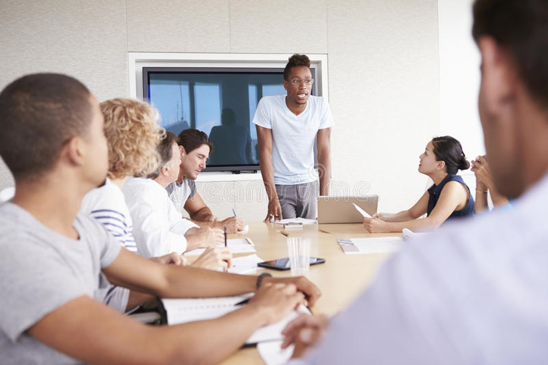 Businessman By Screen Addressing Boardroom Meeting stock photo