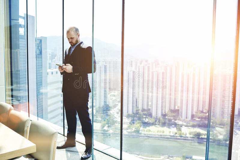 Businessman is searching information on web page via mobile phone. Male CEO is standing in his private office near window with view of metropolitan city with royalty free stock image