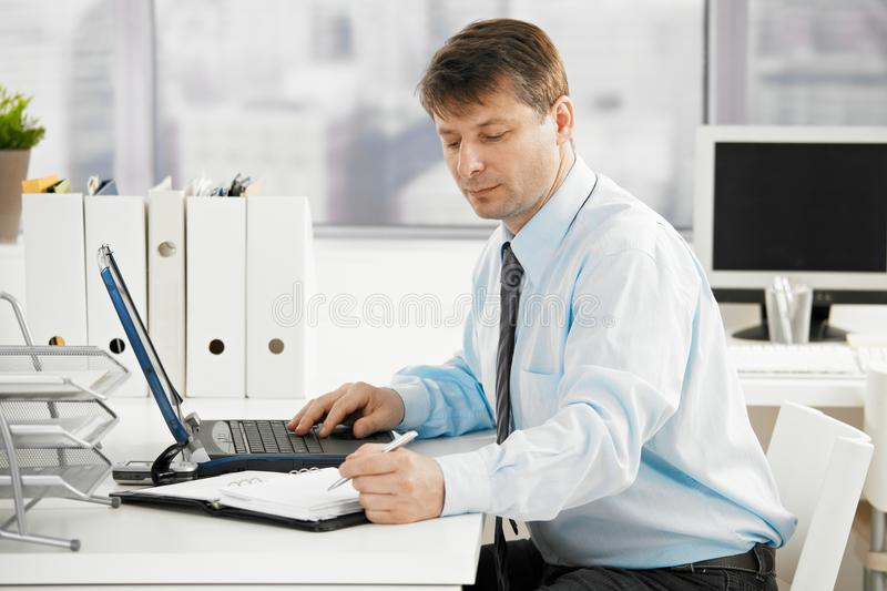 Businessman searching in personal organizer. Businessman working in office, searching in personal organizer stock photography