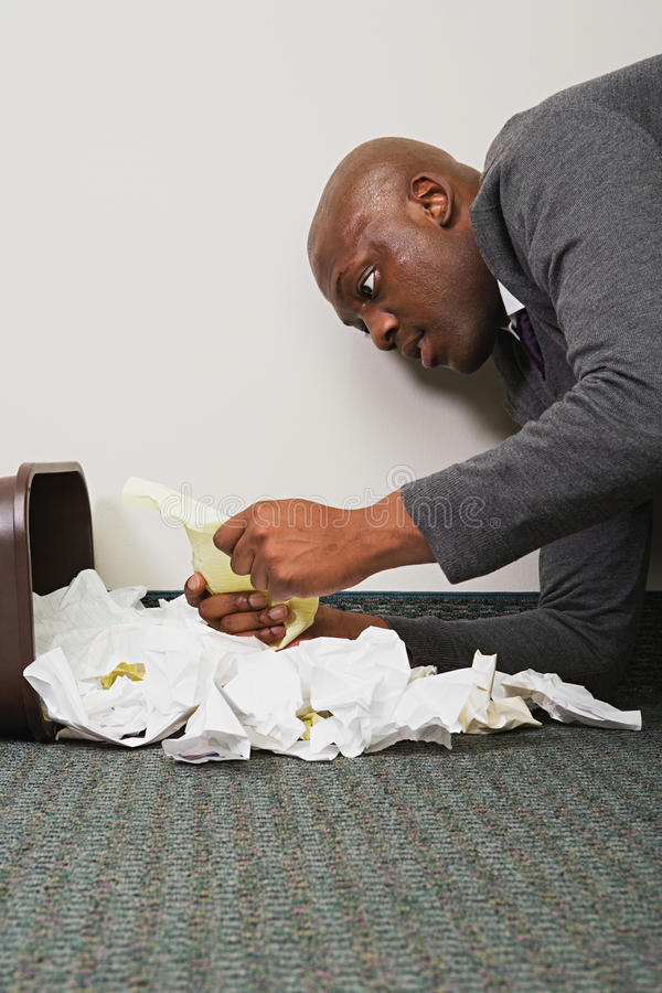 Businessman searching through rubbish bin stock images