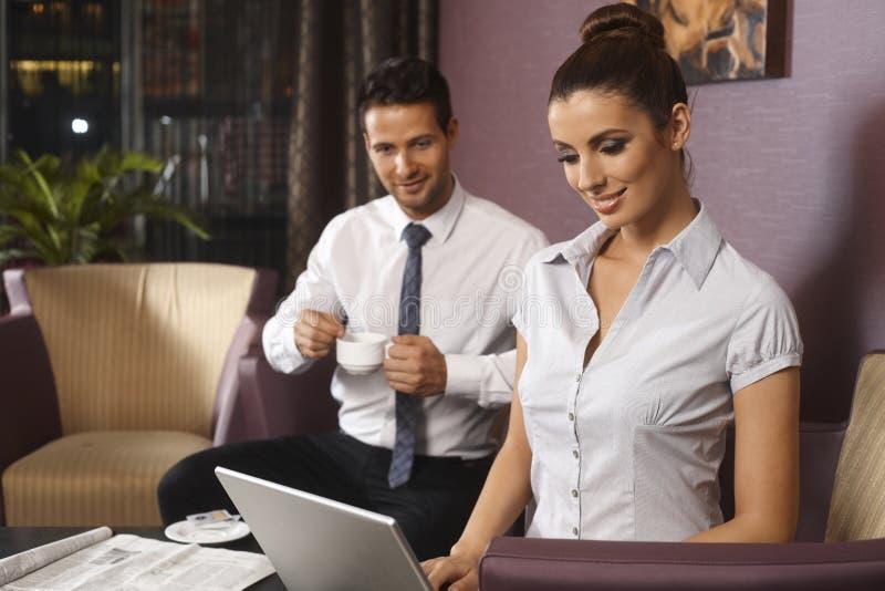 Businessman and secretary at hotel lobby stock photography
